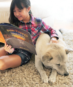 Child reading book to dog